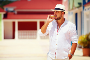 confident man smoking cigar on caribbean street