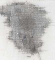 black spot of oil on the white material
