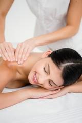 Pretty brunette enjoying a massage smiling