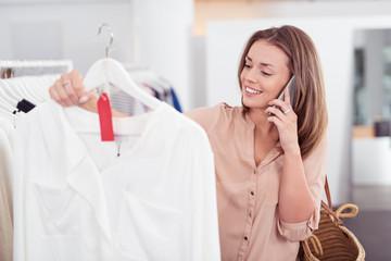 kundin mit handy beim einkaufen in einer boutique