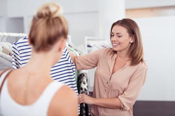 freundliche verkäuferin zeigt einer kundin ein shirt