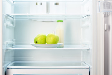Two apples on plate and bottle of yoghurt in refrigerator