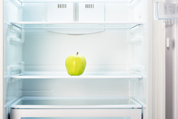 Green apple on shelf of open empty refrigerator