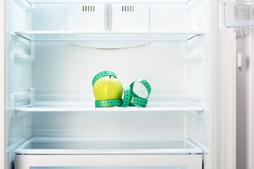 Green apple with measuring tape on shelf of empty refrigerator