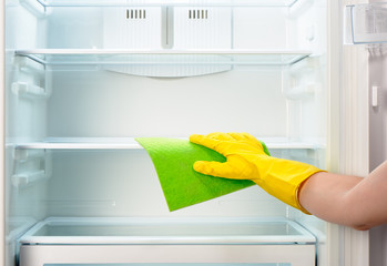 Woman's hand in yellow glove cleaning refrigerator with green rag