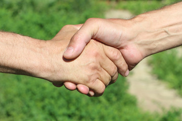 Suntanned male hands make handshake