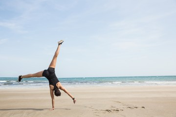 Fit woman cartwheeling on the sand