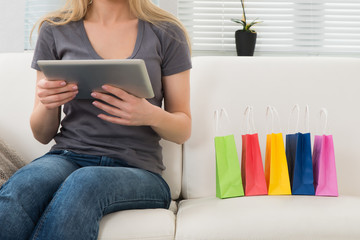 Woman On Sofa With Digital Tablet And Shopping Bags