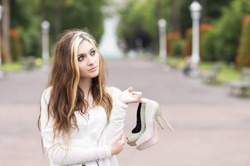 Beautiful elegance girl with heels in hand, outdoor.