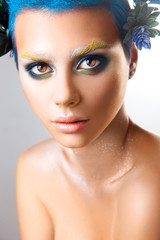 Vertical portrait of beautiful girl with multicolor makeup and b