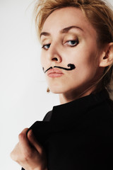young woman with painted mustache wearing jacket