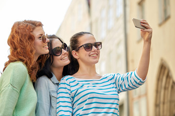 smiling young women taking selfie with smartphone
