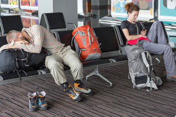 Bodies of people waiting airport terminal Man and woman sitting at chairs waiting lounge airport building sleep on backpack informal sport dress code pants shirt luggage colorful interior background