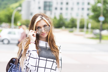 Hipster young woman with sunglasses and backpack in the street.