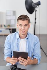 fotograf schaut bilder am tablet-pc an