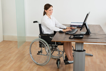 Businesswoman On Wheelchair While Working On Computer
