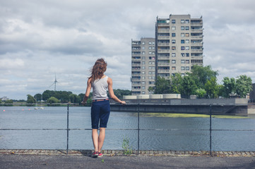 Young woman standing by marina in urban area