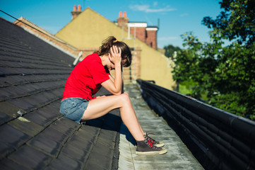Sad young woman sitting on a roof