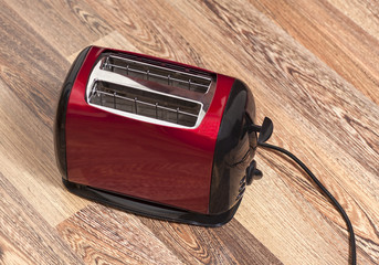 Red toaster on wooden background
