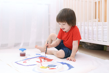 Little lovely child paints with brush and gouache