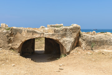 Entrance to an ancient stone burial tomb with Mediterranean Sea in the background at an archaeological site in Paphos, Cyprus.