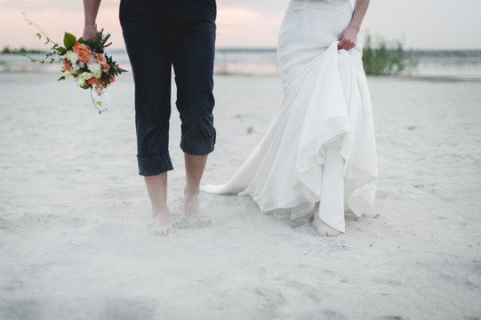 Bride and groom walk on the beach