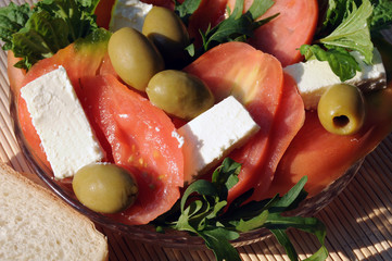 Light summer snack with tomatoes, feta cheese, rocket (eruca sativa), olives, lettuce leaf basil and toast