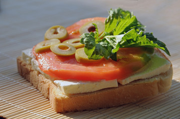 Toast loaded with feta cheese, oxheart tomato slice, olive slices and lettuce leaf basil