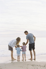Couple playing with their son and daughter on a sandy beach by the ocean.