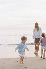 Woman playing with her son and daughter on a sandy beach by the ocean.