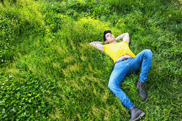 Fit handsome young man relaxing lying on lawn grass