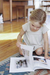 Young girl sitting on the floor, reading a lifestyle magazine.