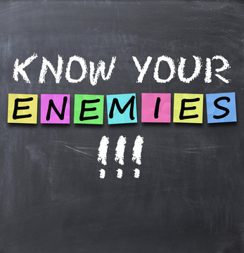 Know your enemies text on a blackboard with chalk and stickers