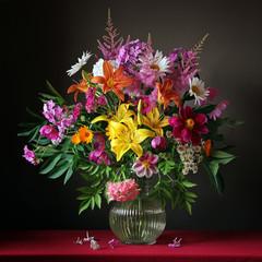 Букет из садовых цветов в кувшине на красной скатерти