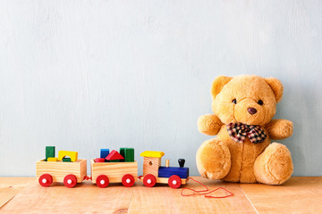 Wooden toy train and teddy bear over wooden floor. retro filtered