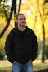 Portrait of the young man on walk on autumn park