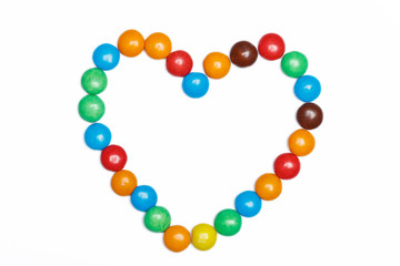 heart frame of colorful candy on a white background with space f