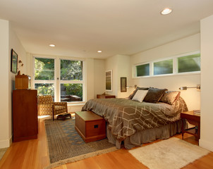 Luxury master bedroom with hardwood floor and brown bedding.
