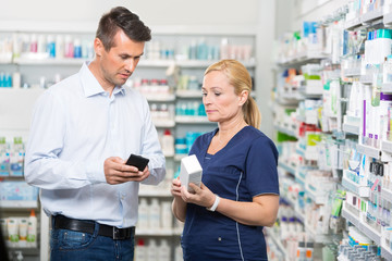 Customer Showing Product Information On Mobile Phone To Pharmaci