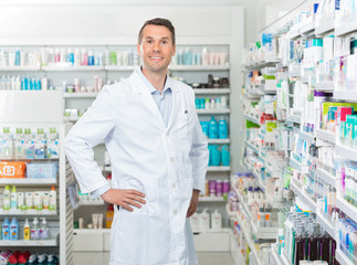 Male Pharmacist Standing With Hands On Hip In Pharmacy