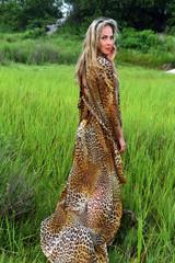 Attractive blond fashion model posing at grass field wearing animal print resort dress.
