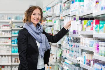 Smiling Female Consumer Choosing Product In Pharmacy