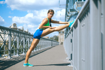 sportswoman stretching her legs on the metal railing of the bridge