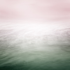 A blurred time exposure of ocean water movement with a glowing center and overlaid with a green to pink color gradient.