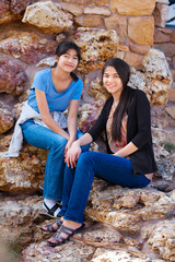 Two young teen girls sitting together on rocky stone seats