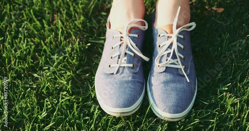 Female Feet In Sneakers Gumshoes Moving And Posing On A Sunlit Green