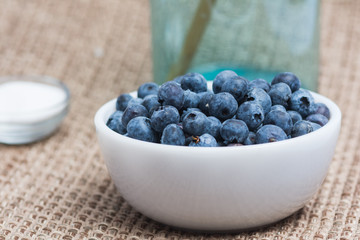 Blueberries in a bowl.  Blue jar and bowl of sugar in the background