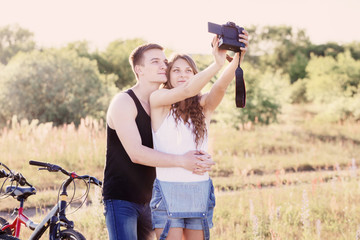 couple with bicycles taking selfie with digital camera