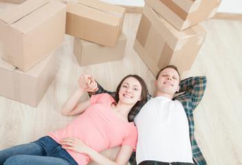 Young couple lying on the floor among cardboard boxes