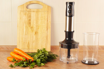 Raw carrots with herbs and a blender on the kitchen table